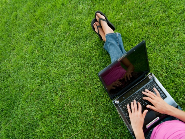 Woman with laptop sit relaxed green grass